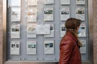 Una joven pasa delante de una agencia inmobiliaria, durante la crisis por el Covid-19.