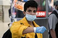 Una mujer muestra su pulsera de control de Covid-19 en el aeropuerto de Kuwait.
