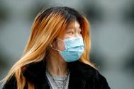 Una mujer con mascarilla pasea por Melbourne.