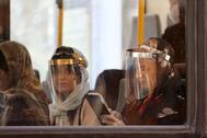 Pasajeros con pantallas protectoras en un bus en Teherán.