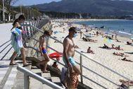 Tres veraneantes acuden con mascarilla a la playa de Samil, en Vigo.