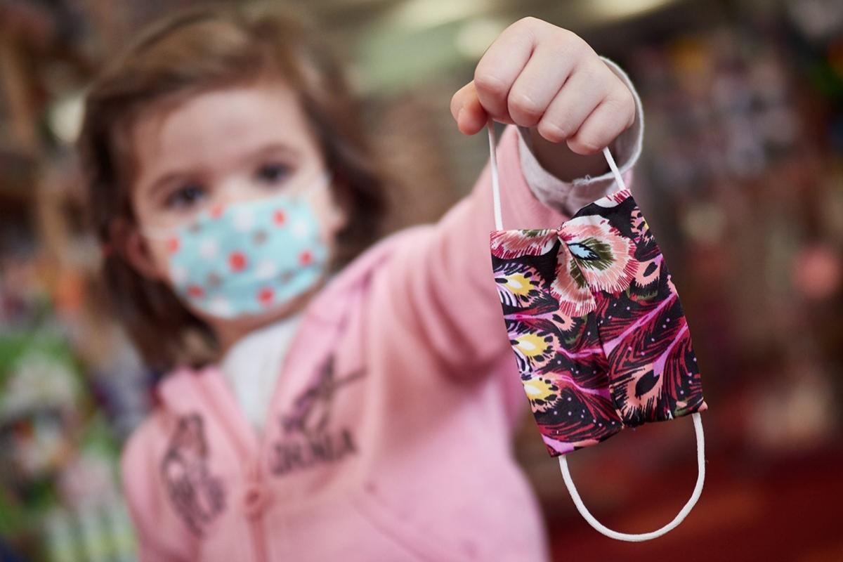 Una niña muestra una mascarilla infantil mientras sale a la calle en el primer día de relajamiento de las medidas de confinamiento.