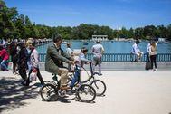 Un padre pasea en bicicleta con su hijo por el Parque de El Retiro de Madrid.