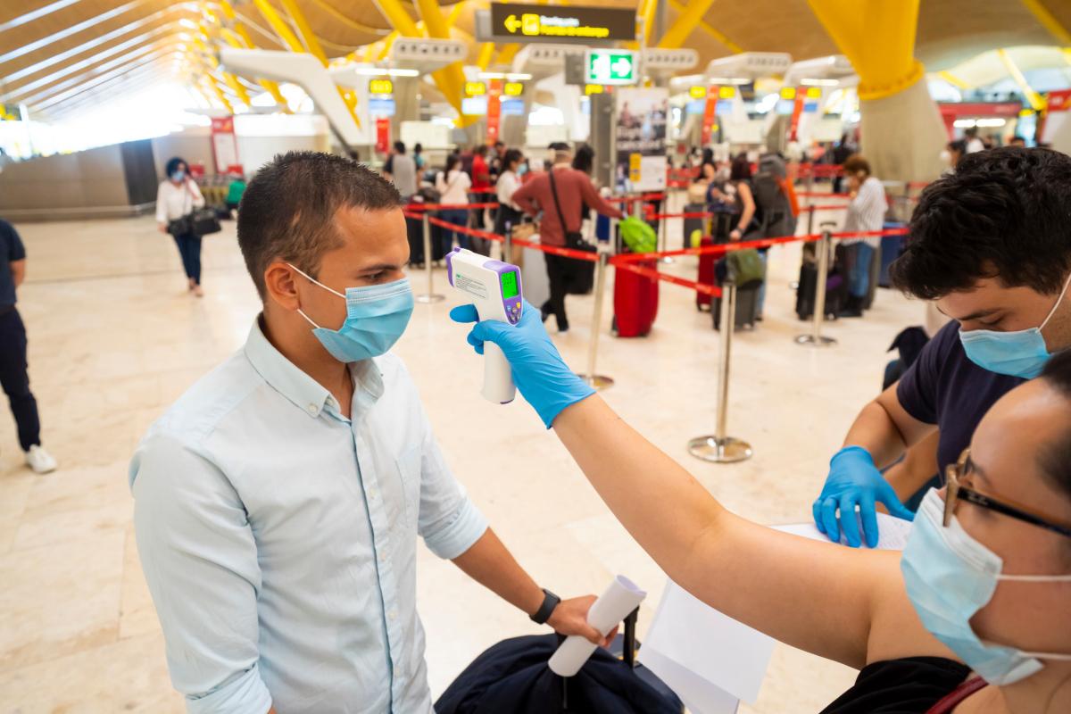 Trabajadores de Aena toman la temperatura a pasajeros recién llegados a Madrid, en el aeropuerto de Barajas.