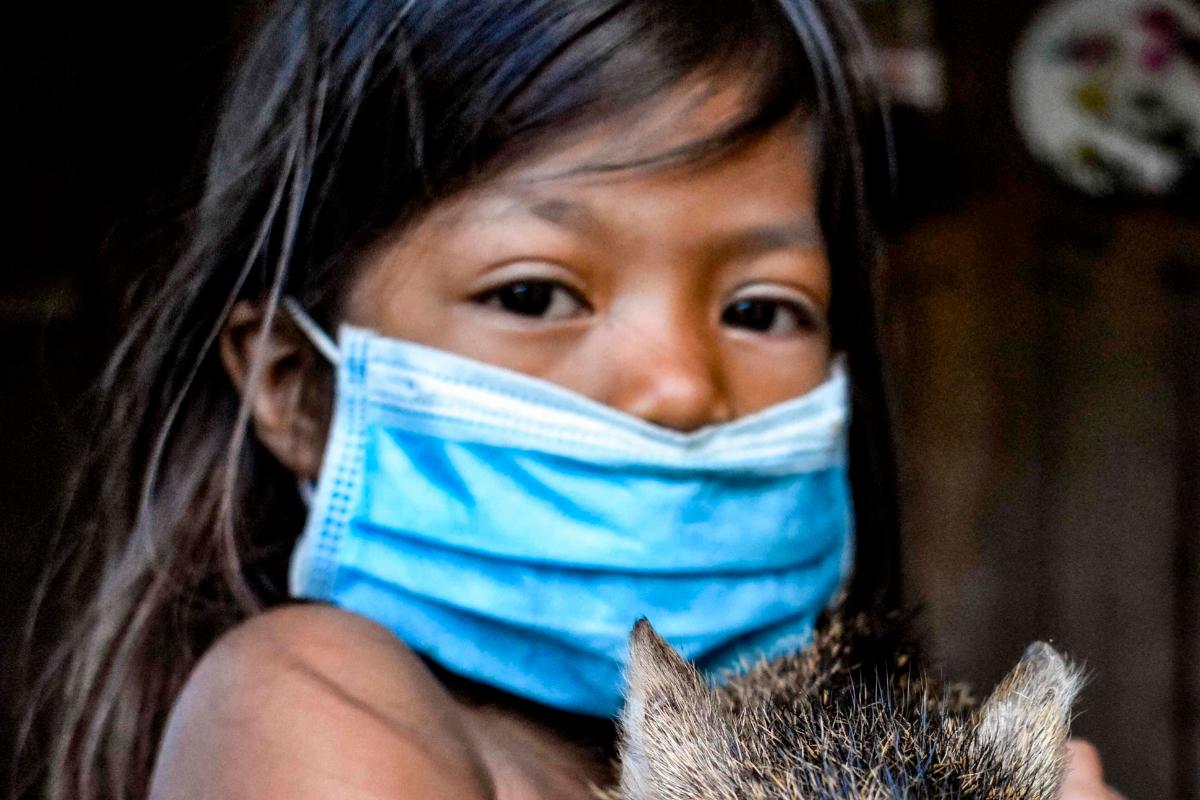 Una niña indígena de la tribu Tikuna posa con mascarilla.