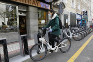 Una usuaria de Bicimad aparca su bicicleta en una estación