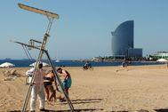 Un trabajador desinfecta la silla del socorrista este jueves en la playa de la Barceloneta