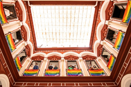 Susana Díaz, asomada al patio de la sede del PSOE andaluz adornado con banderas arcoiris.