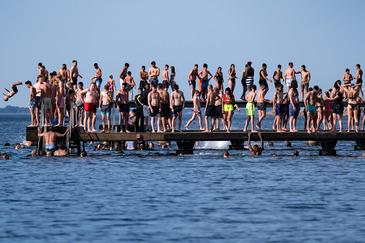 Bañistas suecos en una plataforma marítima en la ciudad de Malmo, sin medidas contra la Covid-19.