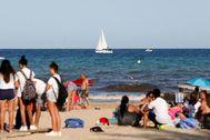 Ciudadanos disfrutando de la playa del Postiguet de Alicante.