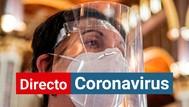 Una mujer se protege del coronavirus con una mascarilla y una pantalla.