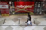 Dos jóvenes pasean por delante de una zapatería en un centro comercial.