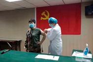 Un sanitario vacuna a un voluntario.