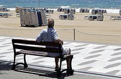 Un hombre observa la inusual estampa de la playa de Benidorm vacía.