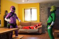 Fotograma del video en el que se ve a los tres superhéroes, el socialista en el sofá.