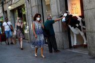 Un hombre acaricia la figura de una vaca con mascarilla en el centro de Madrid