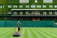 Un operario corta el césped en el All England Tennis Club.