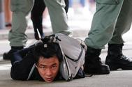 Un manifestante es retenido en el suelo por la policía en Hong Kong.