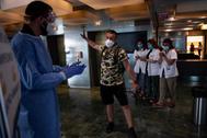 Aplausos para uno de los últimos pacientes de coronavirus que abandonan el Hotel Melia Barcelona Sarria, convertido durante semanas en hospital