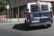 Un coche de la Policía Nacional, en el acceso a un edificio con casos de coronavirus