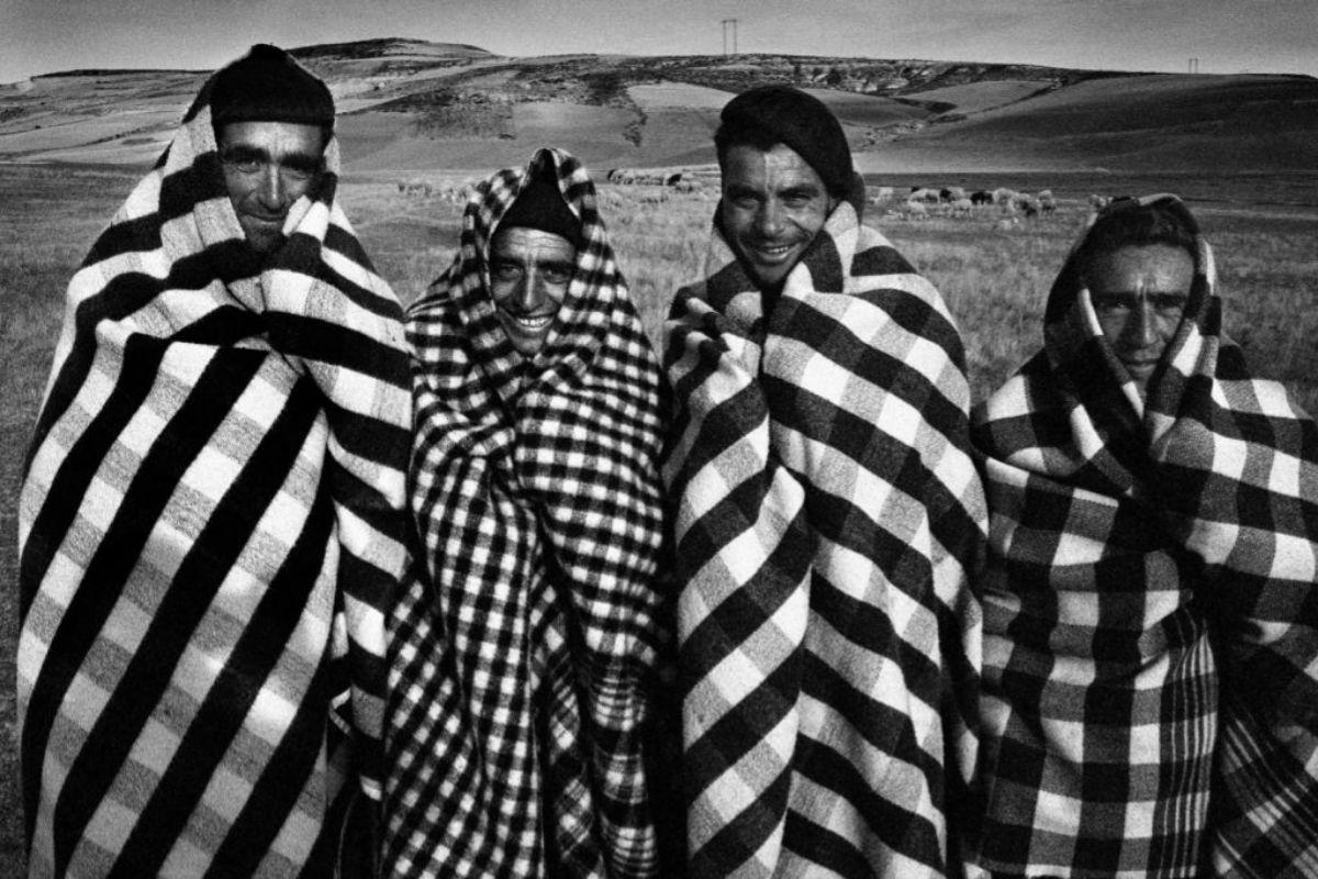 Pastores envueltos en sus mantas en un campo de Castilla retratados por Masats en los años 50.
