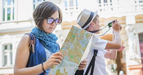 Un par de turistas mirando un mapa y haciendo fotos.