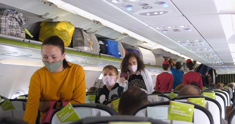 Interior de un avión con pasajeros con mascarilla.