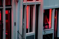 Una prostituta vista a través de una de las ventanas del Barrio Rojo.