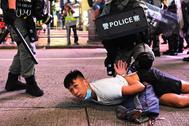 Varios policías detienen a un manifestante durante una protesta en Hong Kong.