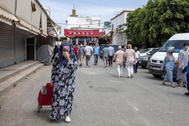 Una mujer con mascarilla por el coronavirus camina por una calle de Rabat.