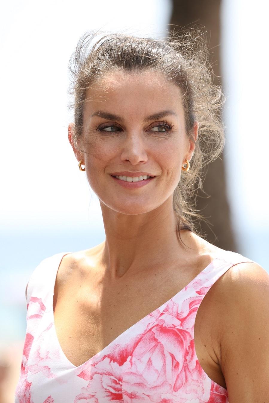 Doña Letizia fiel a los diseñadores gallegos ha elegido un vestido blanco con flores rosas que estrenó para el posado de Palma de Mallorca, en los jardines de Marivent en 2019. El maquillaje muy natural, con un labial ligeramente rosa.