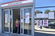 Una mujer sale por la puerta de una oficina del SEPE en Madird