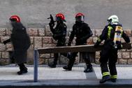 Agentes de la Ertzaintza y del cuerpo de bomberos, durante las protestas en San Sebastián