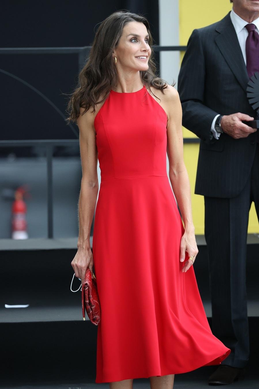 """La Reina Letizia ha vuelto al rojo, uno de sus colores fetiches, <a href=""""https://www.elmundo.es/album/yodona/moda/2017/05/30/592d5877268e3e44738b4725_1.html"""" target=""""_blank"""" rel=""""nofollow"""">al que recurrió por última vez el 19 de junio de 2020 </a> para la reapertura del museo del Prado tras la pandemia del coronavirus. En esta ocasión ha vuelto a revisar su armario y ha elegido este vestido de corte lady y con cuello halter de diseñador desconocido que estrenó en Mallorca en 2019 y que volvió a utilizar en el primer día de su visita oficial a <a href=""""https://www.elmundo.es/album/yodona/moda/2020/02/27/5e57b5e0fdddffaf7a8b4746_17.html"""" target=""""_blank"""">Cuba en noviembre de  ese mismo año. </a>"""