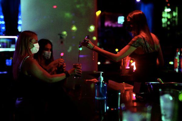 Una bartender sirve dos copas en la sala Oh My Club.