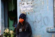 Una mujer espera ante un portal en una calle de Riobamba (Ecuador).