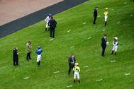 Periodistas entrevistan a jockeys en una carrera de Epsom (Inglaterra).
