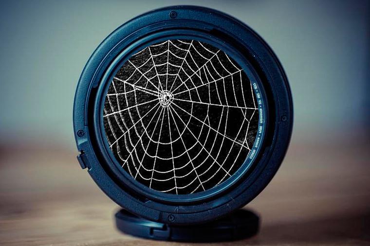 Fotocomposición a partir de un objetivo de fotografía reflex y una tela de araña.