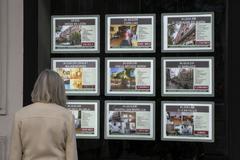 Una mujer mira anuncios de alquiler ante una agencia inmobiliaria.