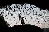 Una mujer hace ruido mientras dirige a los murciélagos lejos de la torre de energía en Hpa-An, estado de Karen.