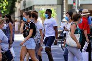 Varias personas, todas con mascarilla, en una calle de Valencia.