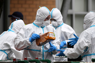Bomberos con trajes de protección reparten comida en un edificio en cuarentena en Melbourne.
