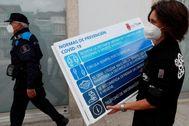 Una mujer coloca un cartel informativo en una calle de Viveiro (Lugo), uno de los municipios confinados.