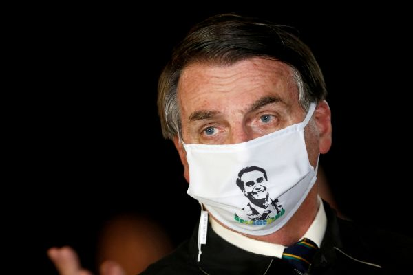 FILE PHOTO: Brazil's President Jair lt;HIT gt;Bolsonaro lt;/HIT gt; speaks with journalists while wearing a protective face mask as he arrives at Alvorada Palace, amid the coronavirus disease (COVID-19) outbreak, in Brasilia