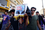 Manifestantes iraquíes portan un ataúd simbólico con la imagen de Hisham al Hashimi durante una protesta en Bagdad.