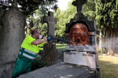 Un trabajador limpia la tumba de Fernando Buesa.
