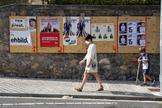 Una mujer y su hijo con mascarillas caminan junto a un espacio electoral en Ordizia.