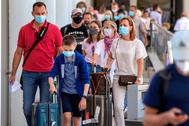 Turistas con mascarilla para el coronavirus en un aeropuerto.