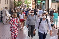 Transeúntes se protegen con mascarillas, este lunes, por las calles de Palma de Mallorca.