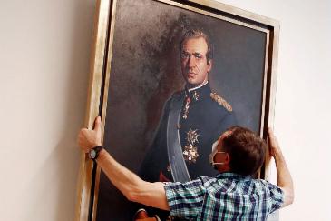 Un hombre retira el retrato de Juan Carlos I del Ayuntamiento de Pamplona.